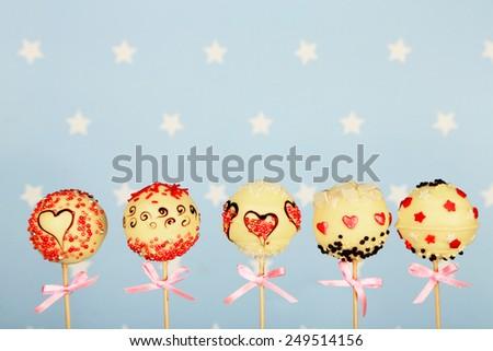 Tasty cake pops on blue background - stock photo