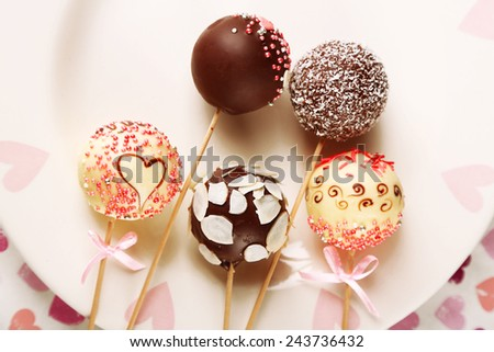 Tasty cake pops on plate, close up - stock photo