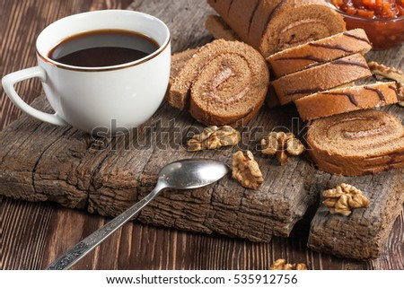 Tasty cake roll and coffee on old wooden table. Rustic style