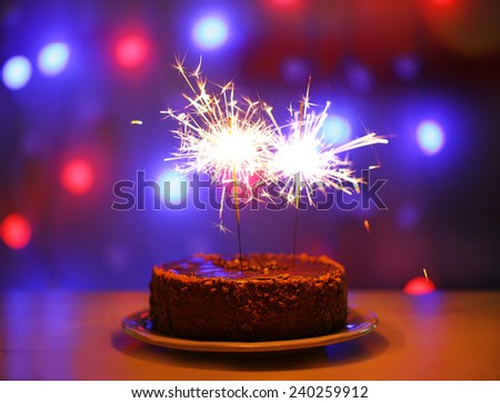 Tasty cake with sparklers on shiny background - stock photo