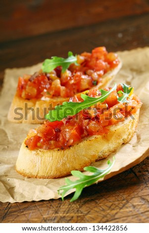 Tasty canape or bruschetta with chopped fresh tomato , onion and seasoning on crusty crisp toasted or grilled baguette garnished with a leaf of rocket on crumpled brown paper - stock photo