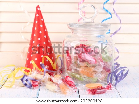 Tasty candies in jar with party hat on table on wooden background - stock photo
