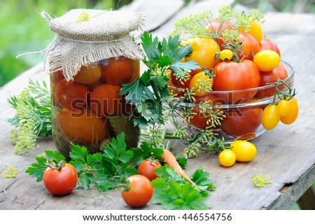 Tasty canned and fresh tomatoes on wooden table