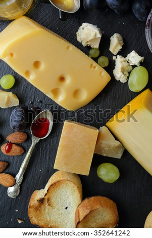 tasty cheese on slate background, top view