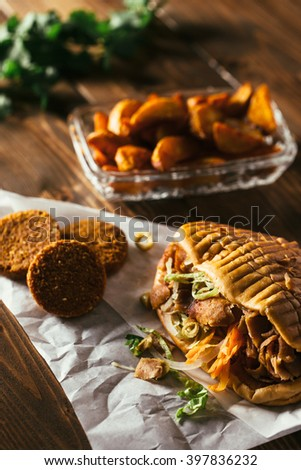 Tasty chicken doner kebab with falafel on a wooden table - stock photo