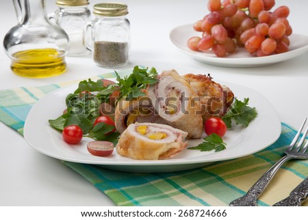 Tasty chicken prosciutto roulade stuffed with cheese and pineapple, served with baby kale, grapes, and cherry tomatoes salad.  - stock photo