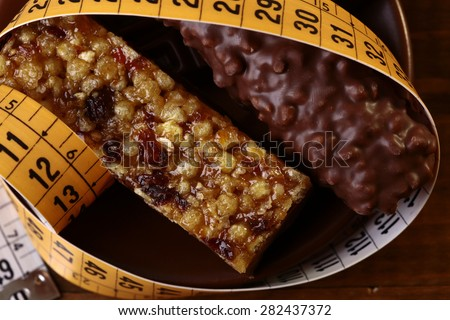 Tasty chocolate bars and peanut brittle with a measuring tape as a symbol of diet closeup, horizontal photo - stock photo