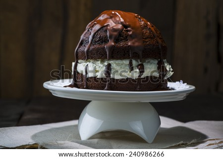 Tasty Chocolate Cake on White Tray with White Cream at the Middle. Served on Top of White Cloth at Wooden Table with Spoon on the Side. - stock photo