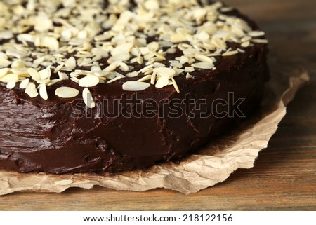 Tasty chocolate cake with almond, on wooden table