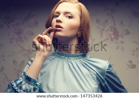 Tasty chocolate concept. Vintage portrait of a glamorous red-haired (ginger) girl in blue dress eating chocolate candy. Retro (old hollywood, classic) style. Close up. Copy-space. Studio shot - stock photo