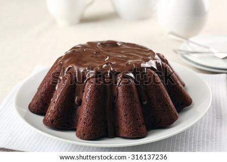 Tasty chocolate muffin with glaze on table close up - stock photo