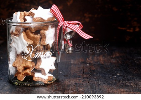 Tasty Christmas Cookies in Transparent Pot with Silver Bells, Isolated on Vintage table Background. - stock photo