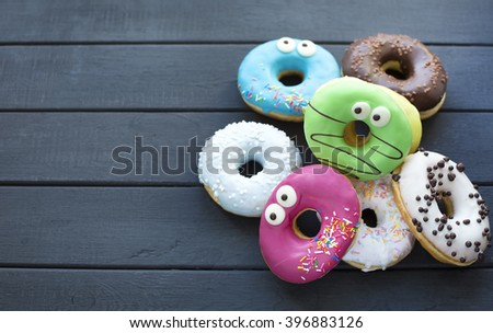 tasty colored donuts on gray wooden background  - stock photo