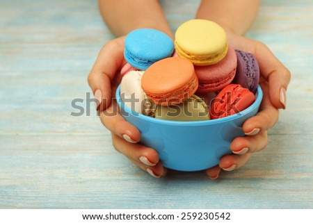 Tasty colorful macaroons in bowl and female hands on color wooden background - stock photo