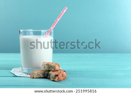 Tasty cookies and glass of milk on color wooden background - stock photo