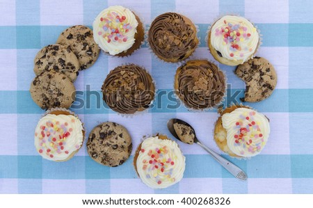 Tasty cookies and muffins cakes with chocolate cream decorated with sugar candies on a blue checkered tablecloth - stock photo
