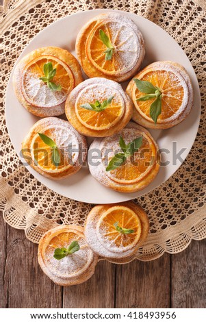 Tasty cookies with oranges, decorated with mint and powdered sugar close-up on a plate. Vertical view from above