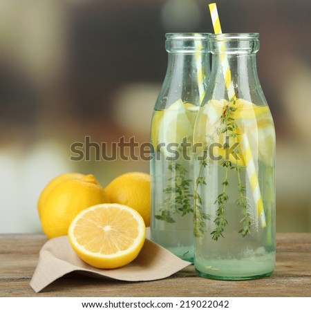 Tasty cool beverage with lemon and thyme, on light background - stock photo