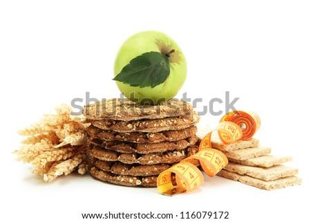 tasty crispbread, apple, measuring tape and ears, isolated on white - stock photo
