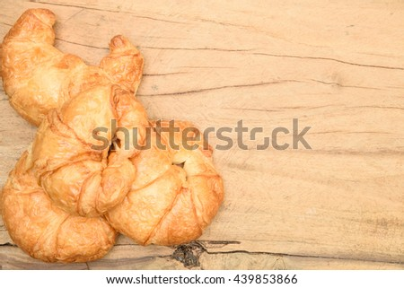 Tasty croissant on wooden background.
