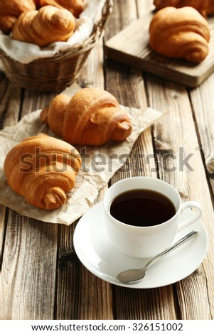 Tasty croissants with cup of coffee on brown wooden background - stock photo
