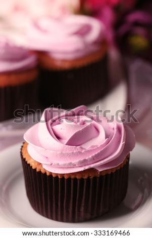 Tasty cupcake on saucer, on light background