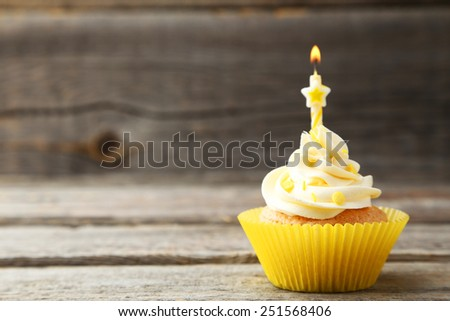 Tasty cupcake with candle on grey wooden background - stock photo