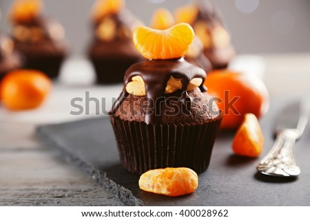 Tasty cupcake with fruits on slate plate over light wooden background - stock photo