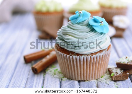 Tasty cupcakes with butter cream, on color wooden background - stock photo