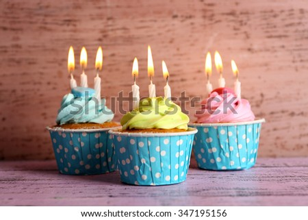 Tasty cupcakes with candles on violet table against wooden background