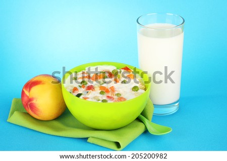 tasty dieting food, fruits and glass of milk, on blue background - stock photo