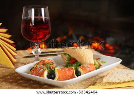 Tasty dinner on a table opposite to a fireplace - stock photo
