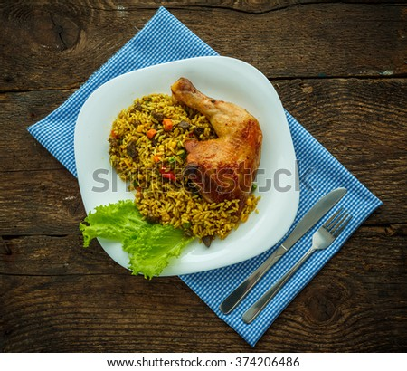 Tasty dish of chicken thigh with rice and salad leaves - stock photo