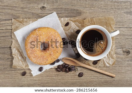 Tasty donut and cup of hot coffee on old wooden table, top view - stock photo