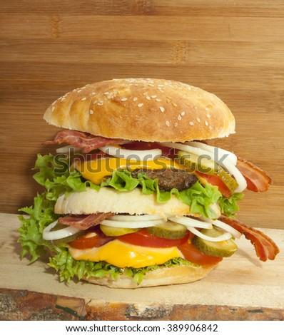 Tasty double homemade hamburger on natural wood - stock photo