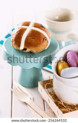 Tasty Easter cross-bun served on a cupcake stand on white wooden background - stock photo
