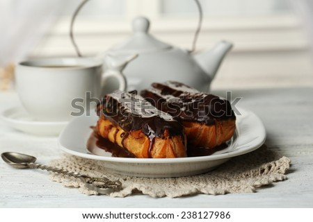 Tasty eclairs and cup of tea on wooden table - stock photo