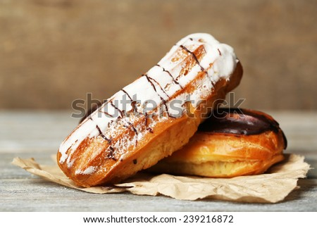 Tasty eclairs on wooden table, close up - stock photo