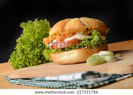 Tasty fish burger with vegetables  - stock photo