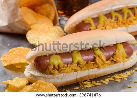 Tasty food for football fans while watching match. Hotdogs with mustard and chips on silver tray. - stock photo