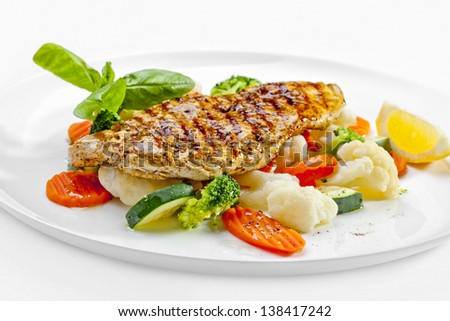 Tasty food. Grilled chicken breasts and vegetables over white background. High quality image - stock photo
