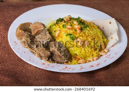 Tasty food on a plate. Rice with meat and sauce. - stock photo