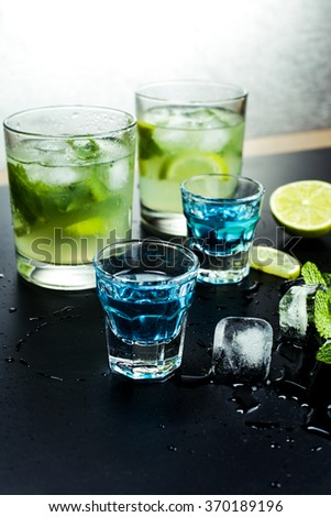 Tasty fragrant refreshing mojito with lime and mint on wet black table in bar or restaurant. Blue liqueur and cocktail mojito.