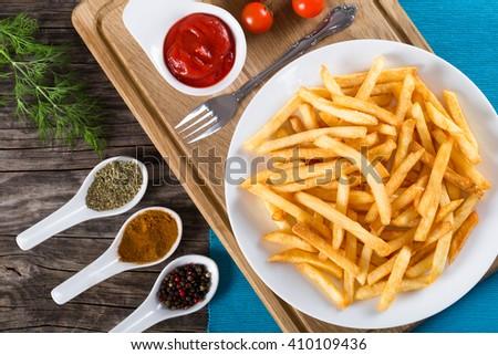 Tasty french fries on white dish, on a cutting board with spices, ketchup,  view from above - stock photo