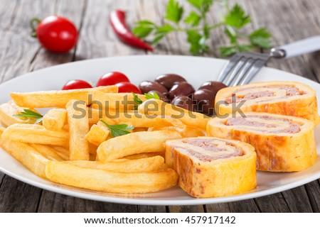 Tasty french fries sprinkled with parsley on white dish with baked cheese meat Roll-Ups, kalamata olives and cherry tomatoes, view from above, blank space left, close-up