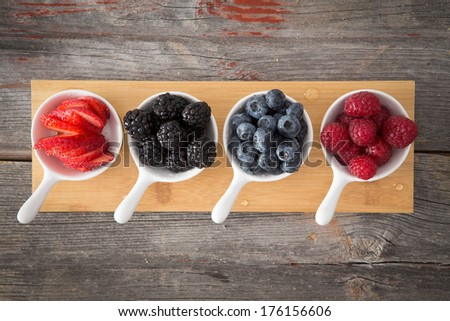 Tasty fresh autumn berries in a rustic kitchen viewed from above in small taster dishes with whole ripe blackberries, blueberries, raspberries and strawberries - stock photo