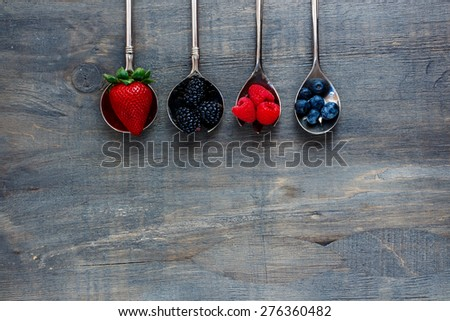 Tasty fresh berries (strawberries, raspberries, blueberries and blackberries) on vintage metal spoons over dark wooden board. Agriculture, Gardening, Harvest Concept. Background with space for text. - stock photo