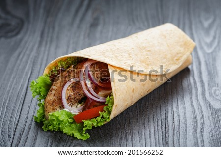 tasty fresh wrap sandwich with chicken and vegetables, on wood table - stock photo