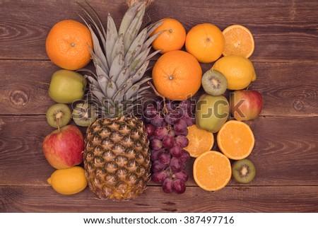 Tasty fruit background with orange, kiwi, grape, apples and lemon on the wooden table - stock photo