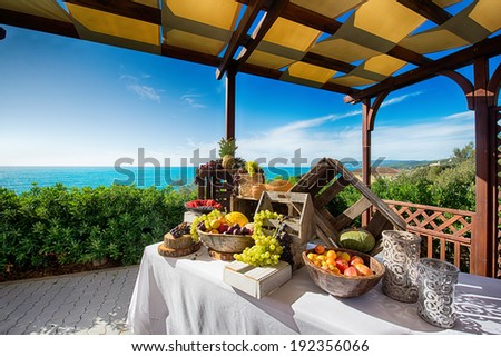 Tasty fruit composition in a balcony on the sea with blue sky - stock photo